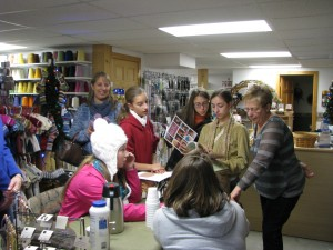 Visitors to Fiber Garden mercantile selecting a knitting pattern